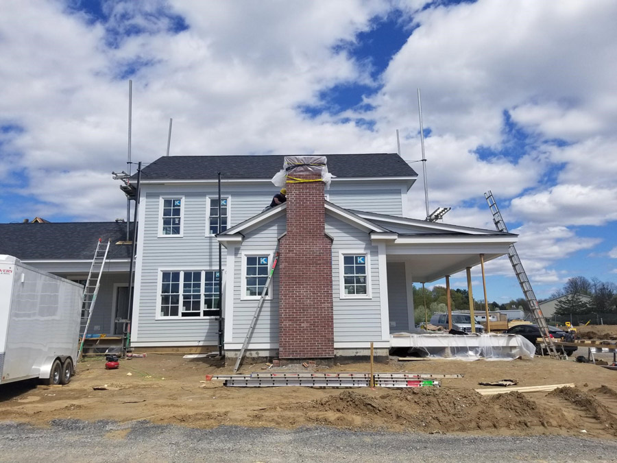 Beautiful construction of The Baldwin model home showing the spacious front porch and chimney